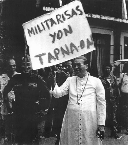 "IN HIS ELEMENT. The late Bacolod Bishop Emeritus Antonio Fortich holds up a ""stop militarization"" sign and still manages to draw smiles from his targets. Photo courtesy of http://negrosnine.com/"