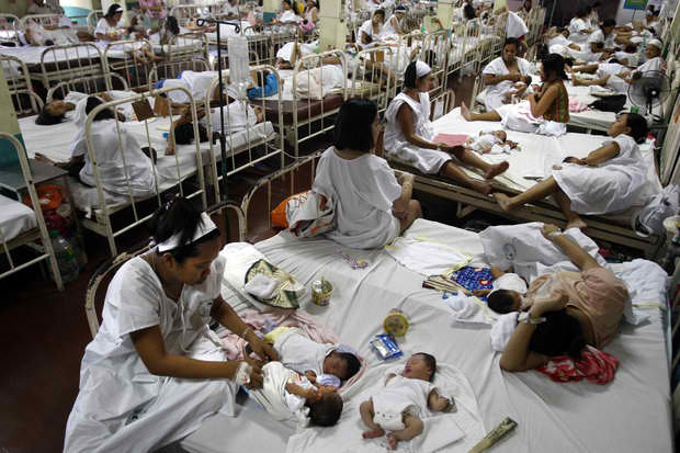 Patients share a bed at congested Fabella Hospital. The poor continue to need to plead with legislators to get health aid.
