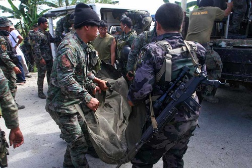 Members of the Philippine National Police carry the body of one of the members of the Special Action Force slain in fighting Mamasapano town, Maguindanao on Monday. More than 30 have been reported killed from the government side following a clash with Muslim rebels. Photo: Reuters via abs-cbnnews.com