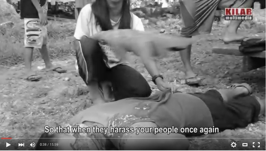 Sheina Campos, 13, keeping insects off the body of her slain father, Dionel, a lumad leader of Lianga, Surigao del Sur. Photograb from Kilab multimedia production,