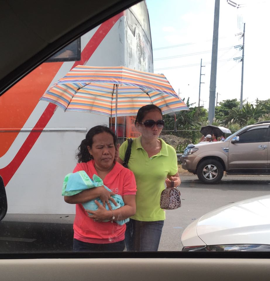 A commuter assists a woman with a baby in her arms as they decide to turn back because of the monstrous traffic on the coastal highway. Photo by Michelle Estor